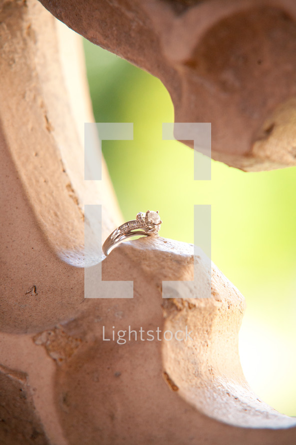 A photo of an engagement ring sitting in the ornate hole in a decorative wall.