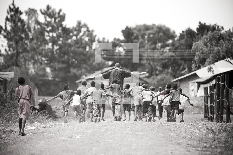 Man walking with children in village