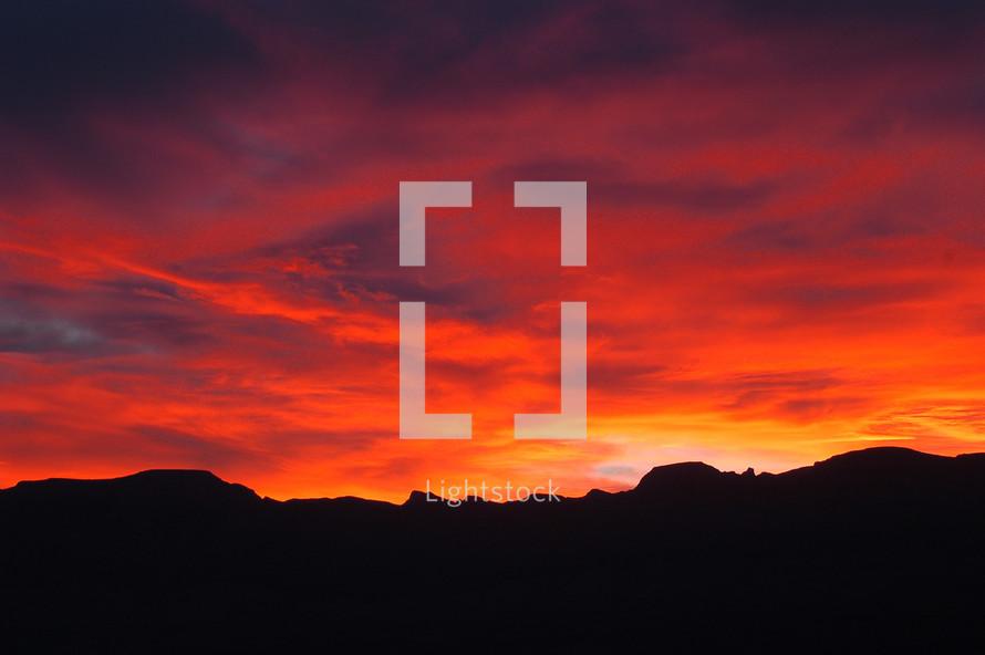 A vibrant and breathtaking sun rises over the ridge of a mountain.