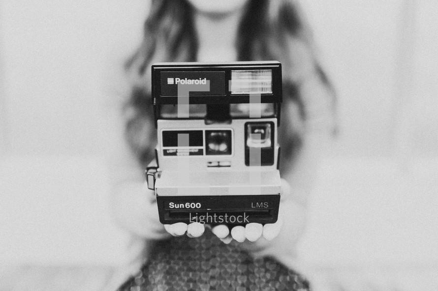 Woman holding Polaroid camera