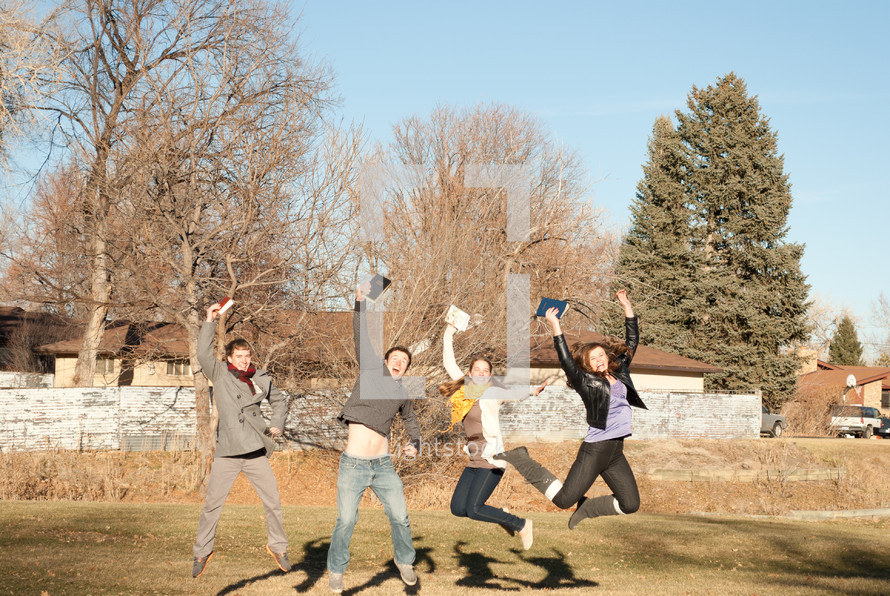 college students jumping up and down holding Bibles outdoors during a Bible study