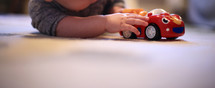 an infant playing with a toy car