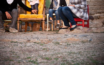 Family sitting in chairs in the dirt outside.