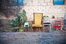 Family chairs and cactus outside by a brick wall.
