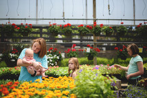 sisters picking out flowers at a garden center