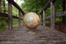 a globe on a weathered wood boardwalk
