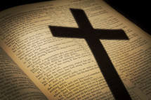 shadow of a cross on the pages of a Bible opened to the passion account