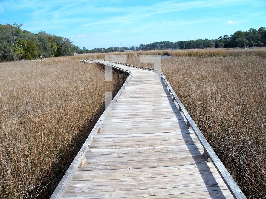 The pass - Narrow foot bridge across the wet marsh lands of Tybee Island, Georgia.