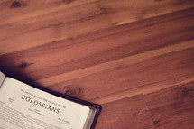 BIble on a wood floor opened to Colossians