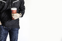 Man in jeans and black jacket with one hand in pocklet, holding red disposable coffee cup with the other.