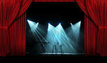 Spotlights on a stage with red curtains.