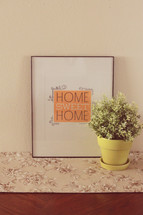 """A framed picture reading """"Home Sweet Home"""" next to a pot of flowers."""