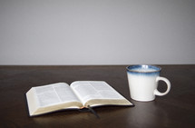 open Bible and coffee mug on a table ready for a Bible study, a small group meeting or teaching moment, as well, they could be preparing for discipleship.