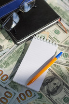 checkbook, cash, and notepad