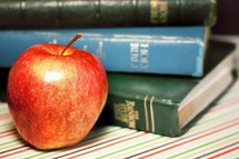 stacked books and an apple