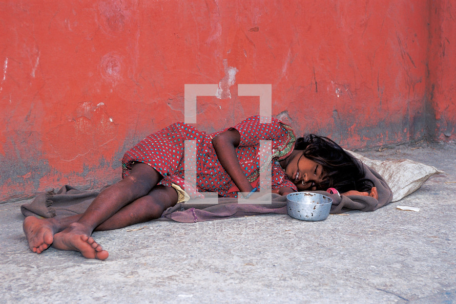 a homeless child sleeping on concrete with begging bowl