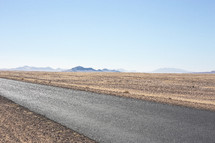 An asphalt road through a barren landscape.