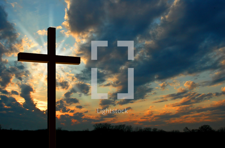 Silhouette of a cross against a sunset.