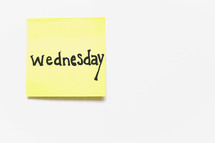 """A yellow sticky note with """"wednesday"""" written in black ink on a white background."""