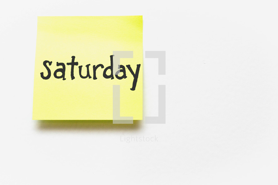 """A yellow sticky note with """"saturday"""" written in black ink."""