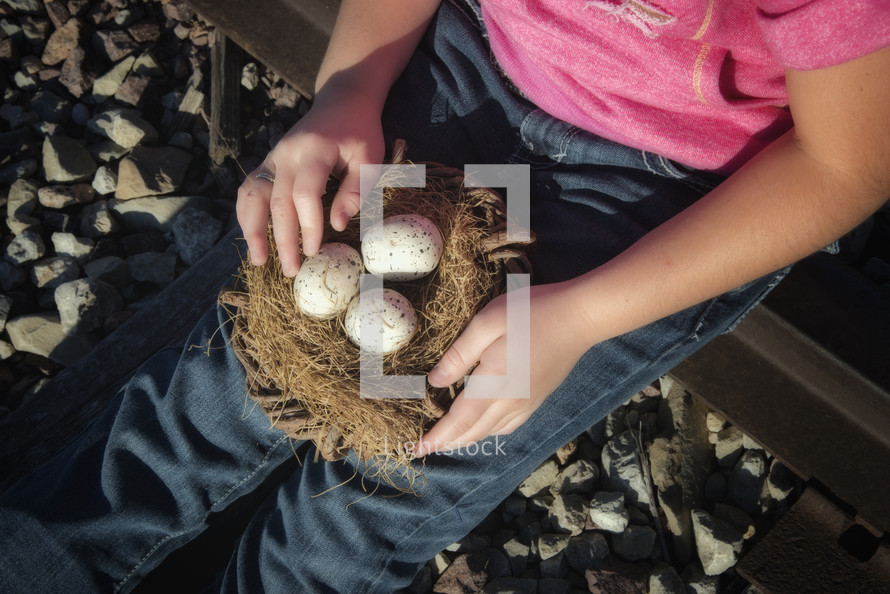 child holding a nest of eggs
