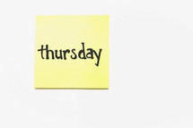 "A yellow sticky note with ""thursday"" written in black ink."