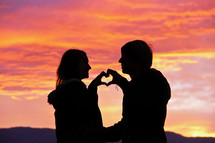 A couple make a heart shape with their hands as a symbol of their love against a backdrop of  the sunset/sunrise.