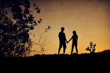 Silhouette of a couple holding hands at sunset.