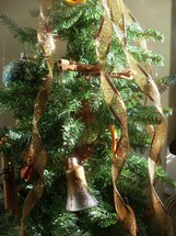 A traditional Christmas tree with silver bells, brown cascading ribbons glowing and bathed in sunlight.
