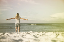 Woman with arms extended staning in the ocean waves.