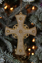 cross ornament hanging on a Christmas tree