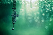cross necklace and a green background