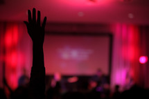 silhouettes, projection screen, congregation, parishioners, standing, raised hands, worship service