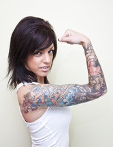 Woman with tattoos on her arm flexing her muscle.
