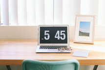 "A laptop computer on a desk reading, ""5:45."""