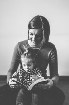 A woman reading to a child in her lap.
