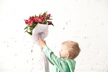 boy holding up a bouquet of flowers