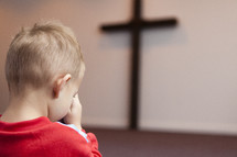 boy child praying in front of a cross