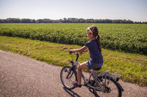 a girl child riding a bike on a rural road in The Netherlands