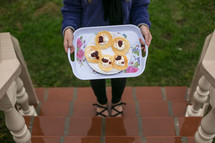 Woman holding tray of pancakes with toppings