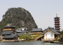 Chinese houses beside water - rock hill behind