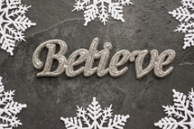snowflake border on gray and word believe
