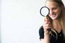 teen girl holding a magnifying glass.