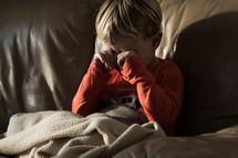 a sleepy toddler boy rubbing his eyes