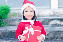a little girl in a Santa suit holding a red gift box