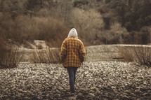 a person walking on gravel terrain