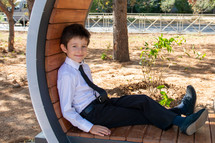 a sweet little boy sitting in a park in dress clothes
