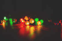 a row of coloured lights reflecting on surface
