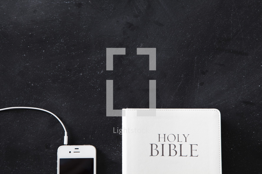 White Bible next to a white cellphone with ear buds plugged in on a chalkboard background.
