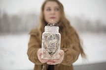 a woman holding a mason jar full of fairy lights
